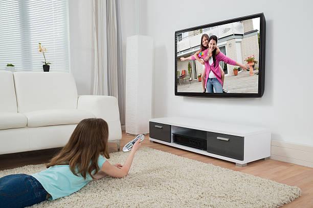 mädchen beobachten film im fernsehen - kids tv zimmer stock-fotos und bilder