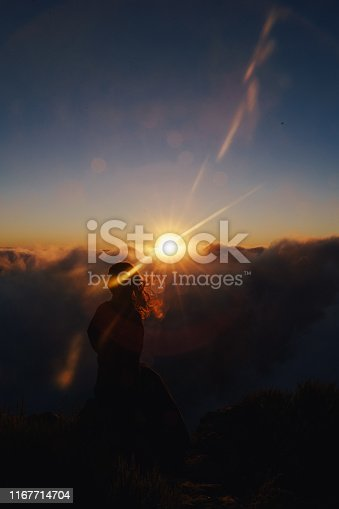 Beautiful girl silhouette watching cloudy sunrise on top of the mountain. Medium close up of female slim body with long hair blowing in the wind. Colorful sky