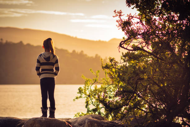 Girl watching sunset over Lake Derwentwater near Keswick, England stock photo