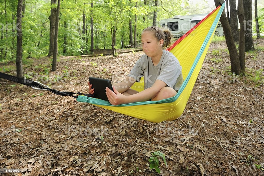 Girl watching tablet computer in campground hammock royalty-free stock photo