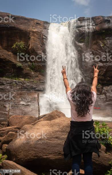 Photo of girl watching the waterfall falling from mountain too at morning from low angle