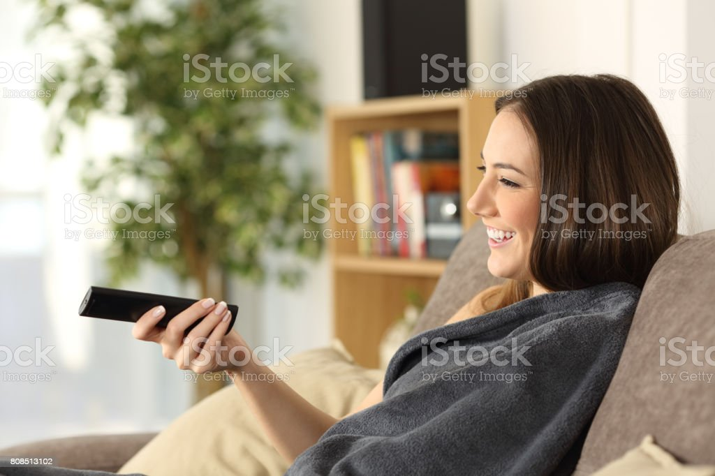 Girl watching tv covered with a blanket stock photo