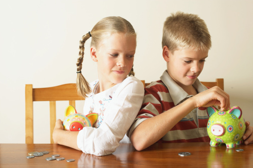 Girl (10-12) watching twin brother drop coin into piggy bank