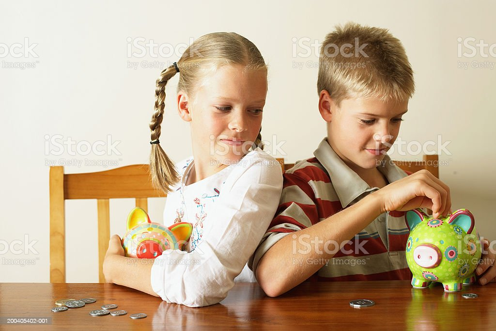 Girl (10-12) watching twin brother drop coin into piggy bank stock photo