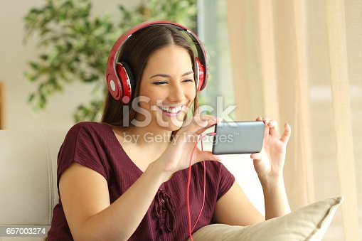 istock Girl watching videos in a smart phone with headphones 657003274
