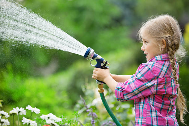 girl watering flowers in garden with hose - garden hose stock pictures, royalty-free photos & images