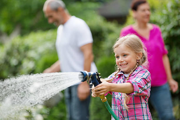 Girl watering plants in garden, family in background stock photo