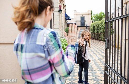 istock Girl waving goodbye to mother outside school 996963958