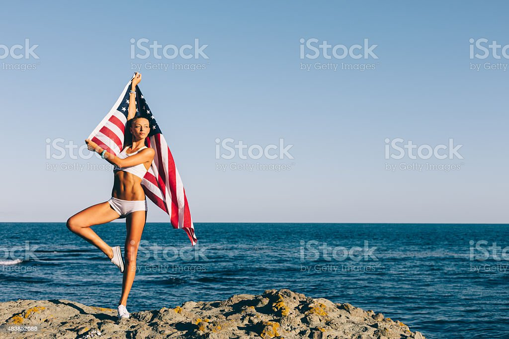 Girl waving the american flag on a rocky beach stock photo