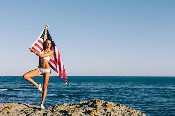 Girl waving the american flag on a rocky beach stock photo