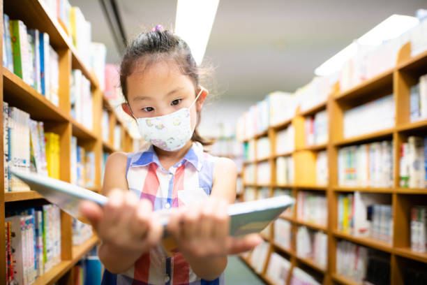 Girl wearing a mask chooses a book stock photo