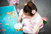女の子が浴衣を着て日本の夏祭りをお楽しみください。