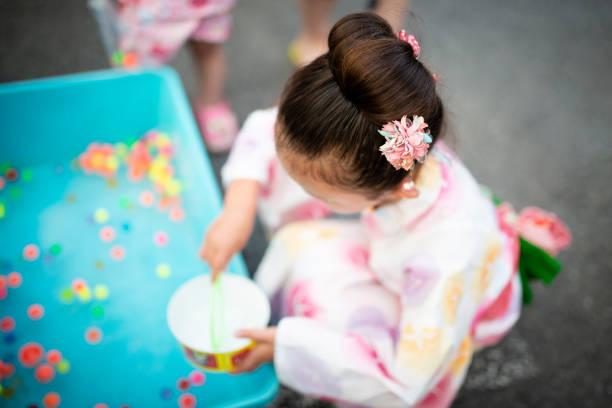 女の子が浴衣を着て日本の夏祭りをお楽しみください。 - 七夕の写真 ストックフォトと画像