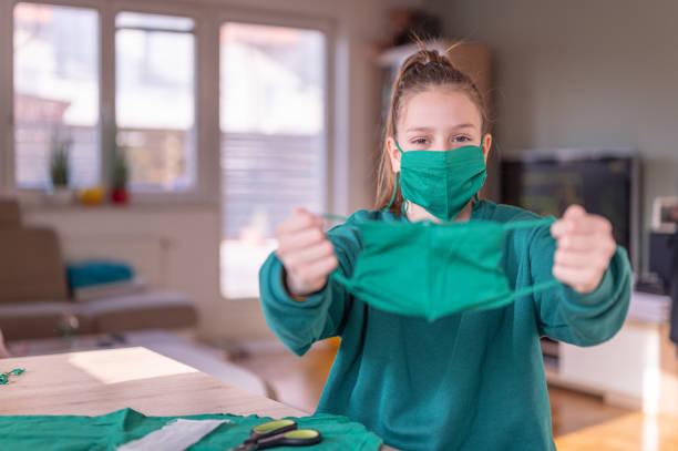 Mädchen tragen und halten eine DIY schützende Gesichtsmaske – Foto