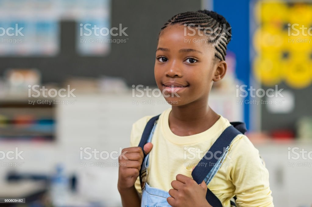 African young girl with blue backpack looking at camera. Pretty and...