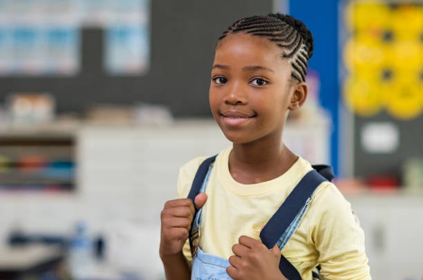Girl wearing backpack at school African young girl with blue backpack looking at camera. Pretty and satisfied black schoolgirl with rucksack smiling in class. Portrait of beautiful school girl standing in classroom. 8 9 years stock pictures, royalty-free photos & images