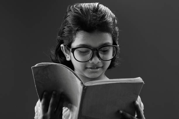 Girl wearing big spectacle reads a book - Photo