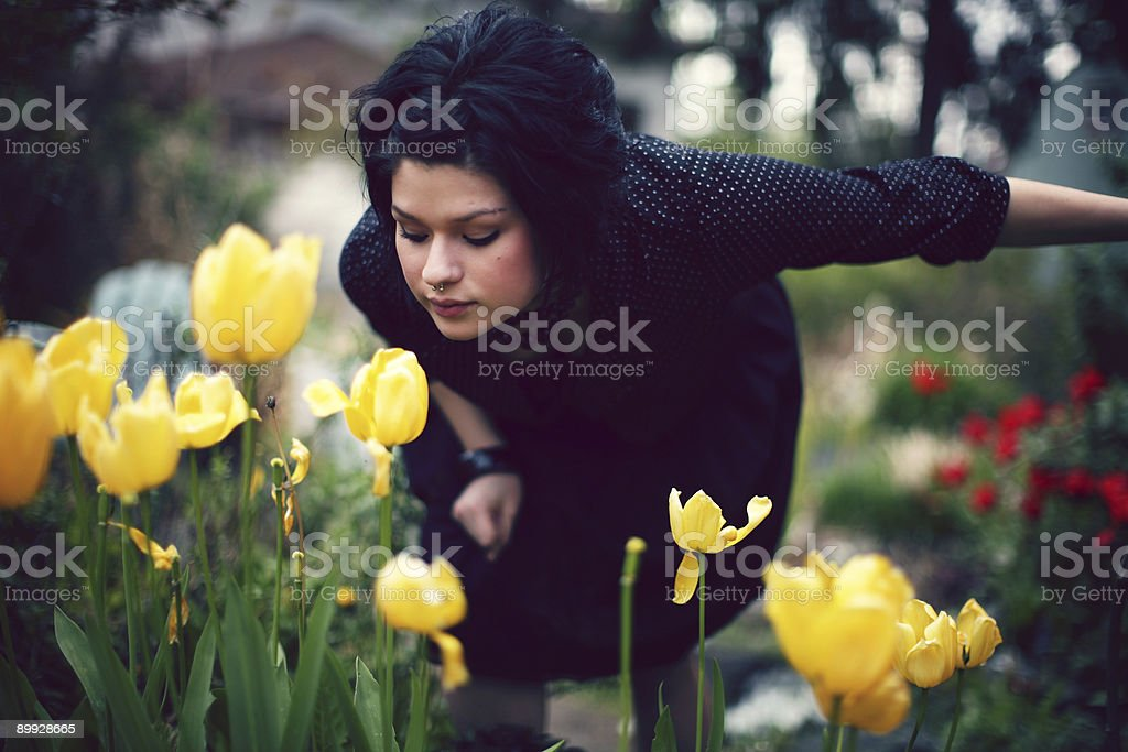Girl Wearing black Clothes Bent Over Smelling Yellow Flowers royalty-free stock photo