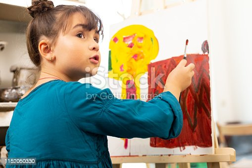 Talking and coloring. Cute dark-haired girl wearing blue dress talking and coloring picture