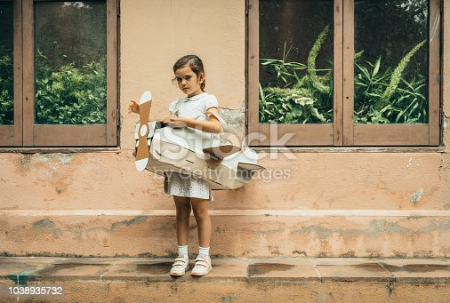 Girl wearing cardboard airplane