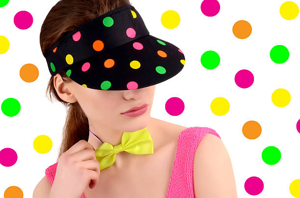Girl wearing colorful polka dotted visor and neon green bowtie. stock photo