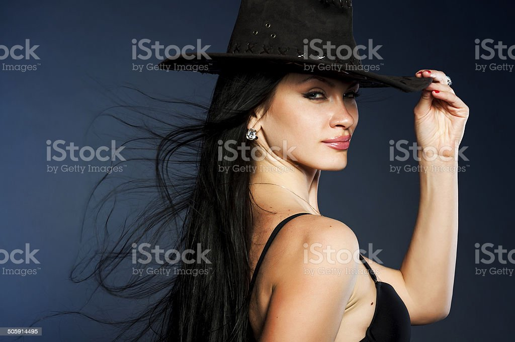 Girl wearing cowboy hat on blue background stock photo
