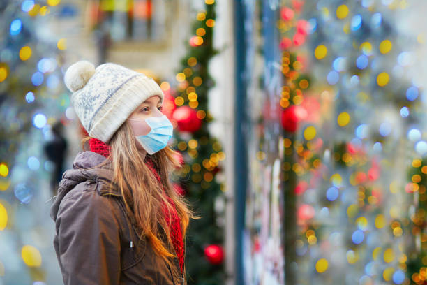 Girl wearing face mask on a Parisian street or at Christmas market stock photo