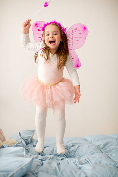 girl wearing fairy costume jumping on bed. - fairy wand stock photos and pictures