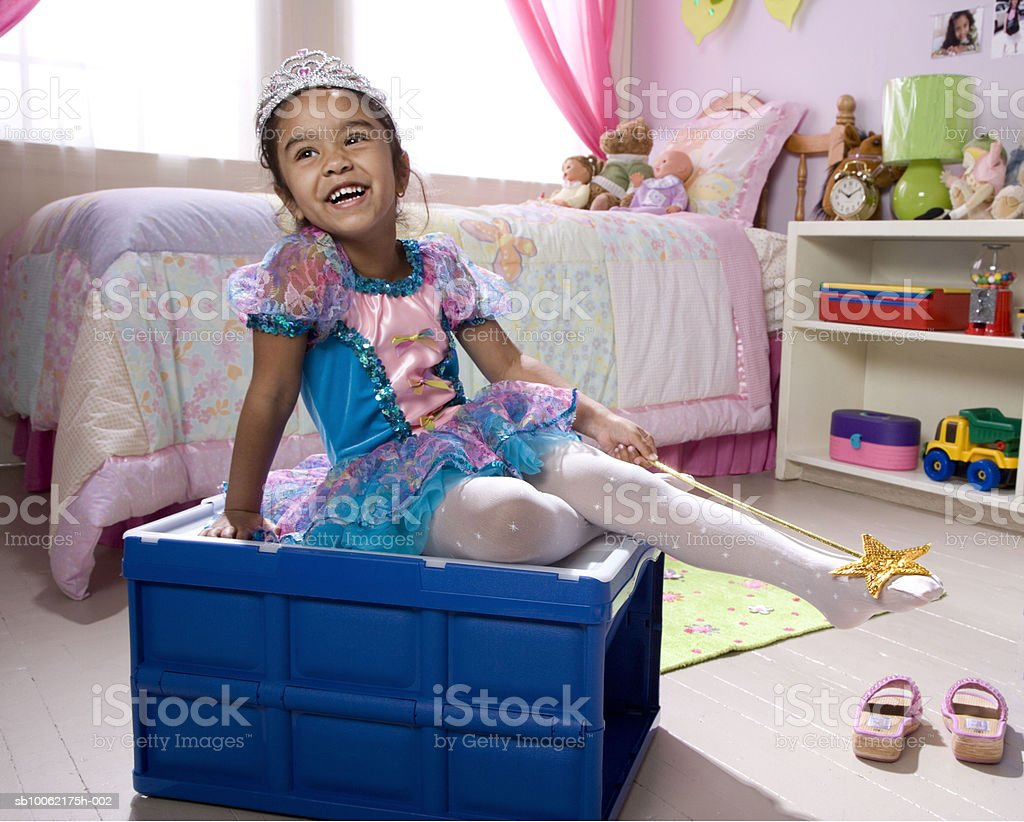 Girl (4-5) wearing fairy costume sitting on stool, smiling foto de stock libre de derechos
