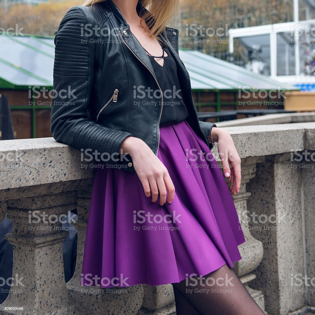 Girl wearing fashionable outfit with black leather jacket and skirt stock photo