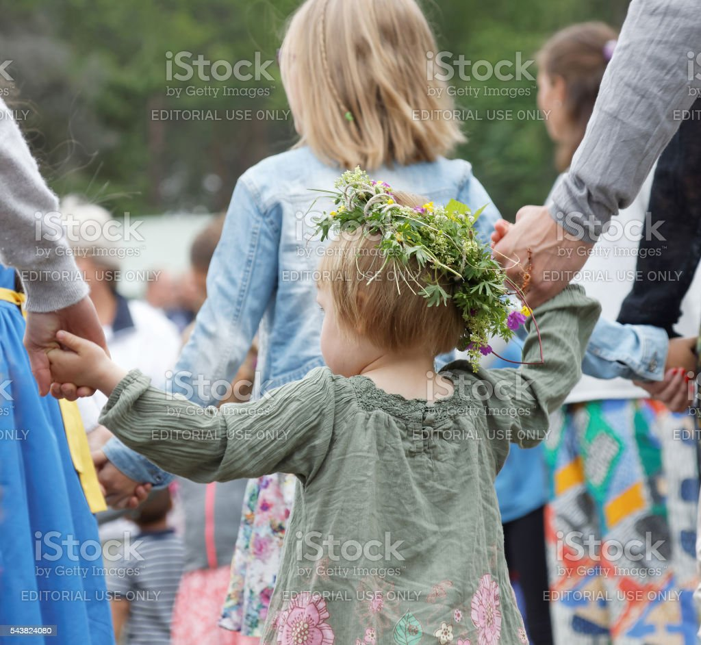 Girl wearing flowers in the hair holding hands and dancing stock photo