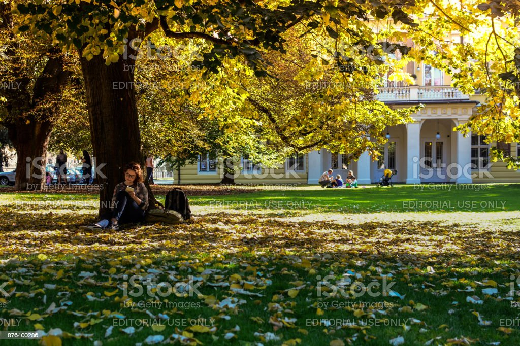 Girl wearing glasses sitting under the tree in autumn park and writing something in her notebook stock photo