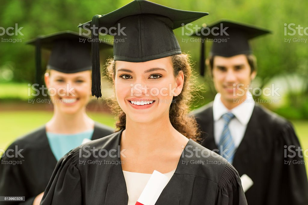 Girl Wearing Graduation Gown Smiling With Students In Background ...