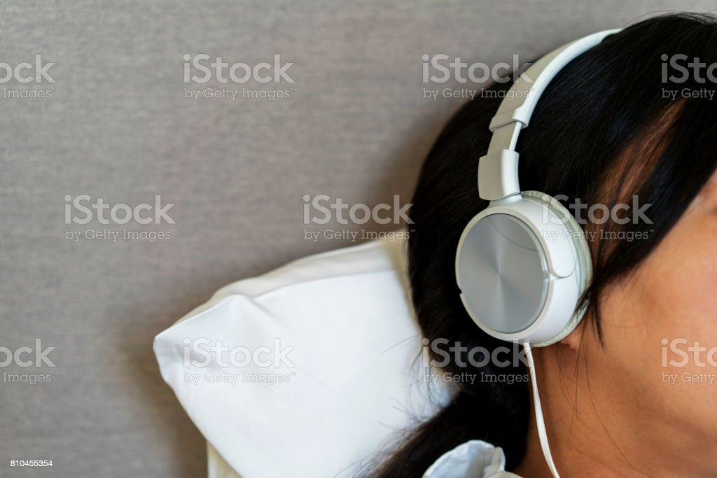 girl wearing headset listening music, on bed stock photo