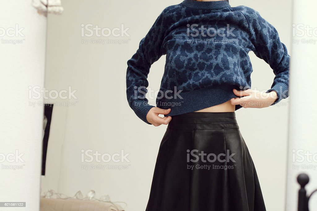 Girl wearing knitted sweater in front of mirror. stock photo