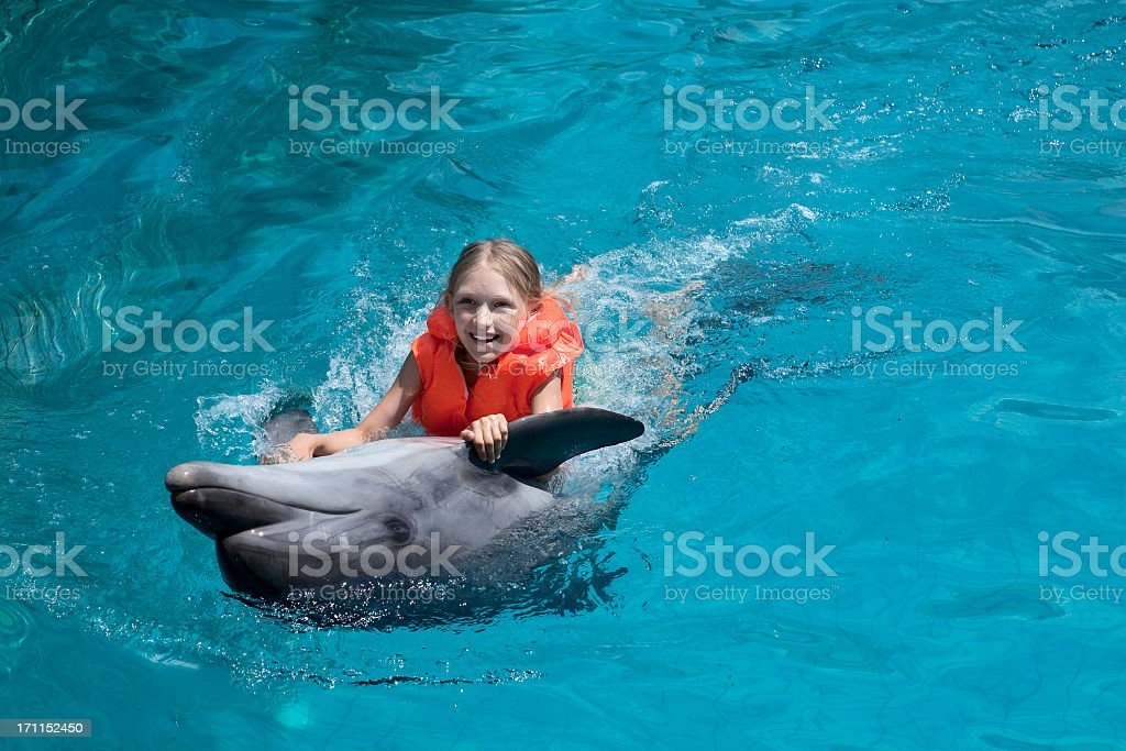 Girl wearing lifejacket with dolphin in clear water stock photo
