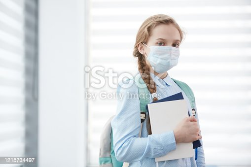 Waist up portrait of cute schoolgirl wearing face mask during epidemic and looking at camera while posing against window holding books, copy space