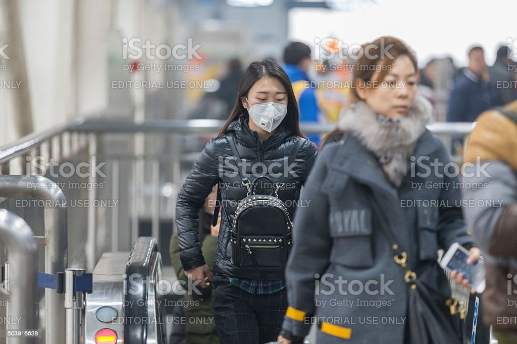 Girl wearing mouth mask with filter against air pollution, Beijing stock photo