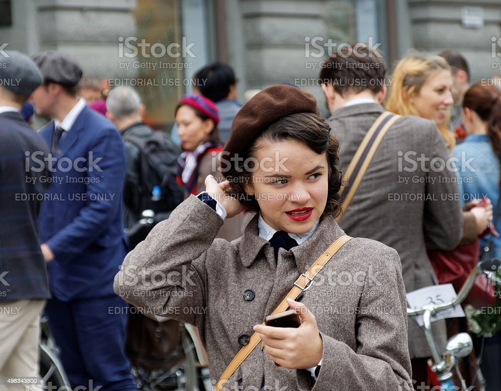Girl wearing old fashioned tweed clothes fixing the hat stock photo
