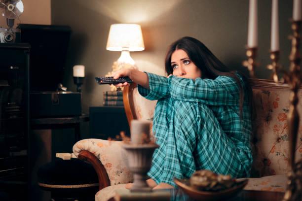 girl wearing pajamas watching tv in her room - noia foto e immagini stock