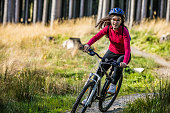 istock Girl wearing protective gear riding bike on forest trail 465663248