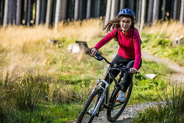 Girl wearing protective gear riding bike on forest trail Girl riding bike  mountain biking stock pictures, royalty-free photos & images