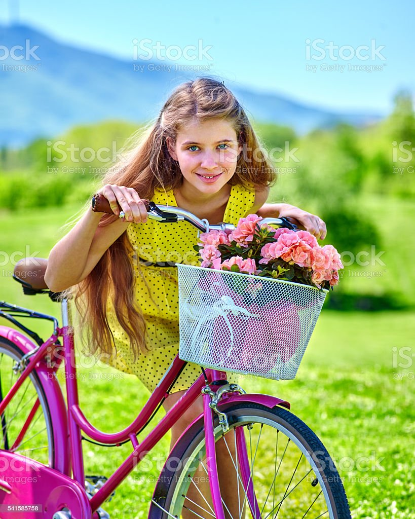 Girl wearing red polka dots dress rides bicycle into park. stock photo