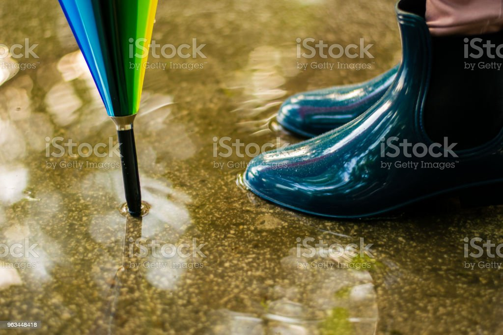 Girl wearing rubber boots and has colorful umbrella - Zbiór zdjęć royalty-free (But z cholewką)