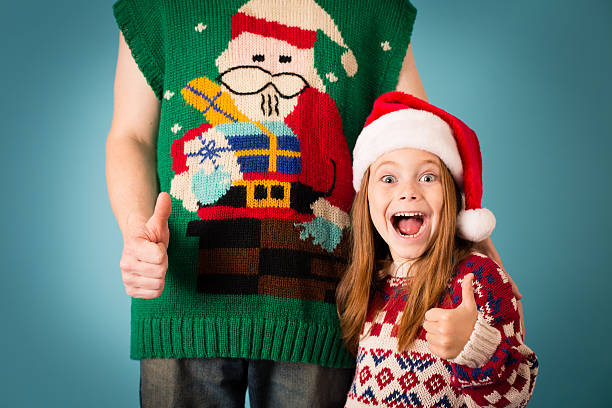 girl wearing santa hat and ugly sweater standing with man - ugly girl stock photos and pictures