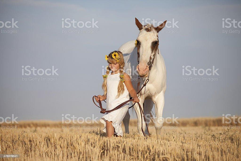 Girl Wearing Summer Dress and Sunflowers Walking Horse stock photo