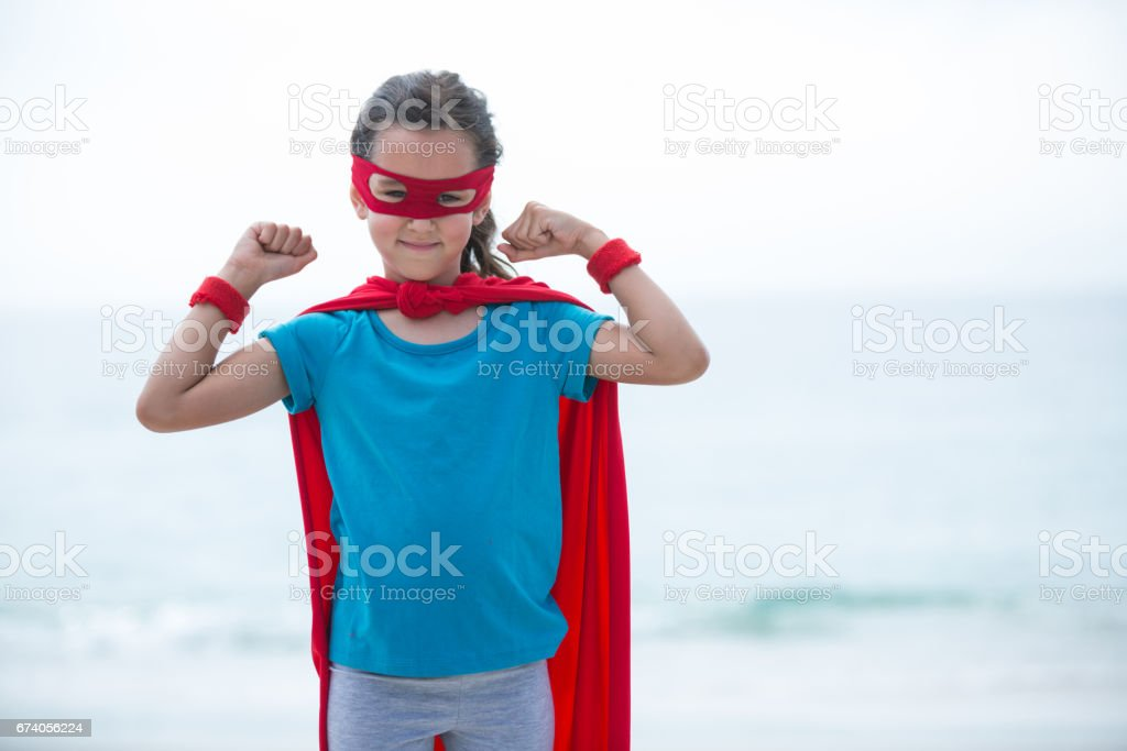 Girl wearing superhero costume flexing muscles at beach royalty-free stock photo