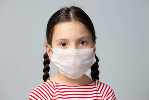 Mädchen trägt chirurgische Maske – Foto