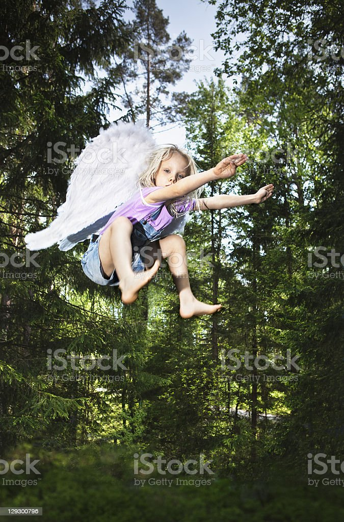 Girl wearing wings and jumping in forest stock photo