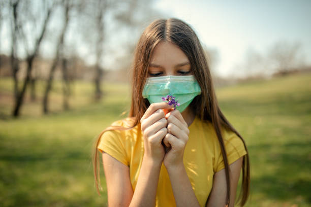 Girl wears protective mask outdoors and smelling flowers stock photo